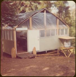"Temporary cabin built with 2x4s, tar paper, and plastic sheeting and marked ""Iona Hall,"" summer 1977"