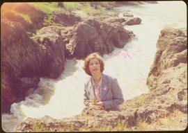 Minister Iona Campagnolo holds bouquet of wildflowers with Moricetown Canyon in background, summer 1977