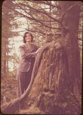 Minister Iona Campagnolo poses beside tree growing from decaying stump, Queen Charlotte City, BC
