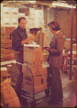 Minister Iona Campagnolo discusses freight costs with storekeeper Werner Funk, Queen Charlotte City, August 1977