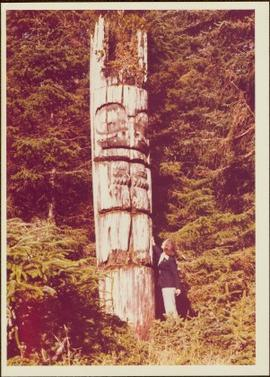 Iona Campagnolo posing beside a carved memorial pole, Ninstints, Anthony Island, Haida Gwaii, September 1977
