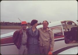 John Lapadat, Minister Iona Campagnolo, and Carmen Graf link arms in front of a small plane, Smithers, BC
