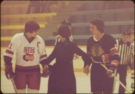 Minister Iona Campagnolo standing on ice, holding the hands of two opposing hockey players, one w...