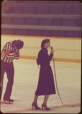 Minister Iona Campagnolo speaking into microphone on ice, with referee in background