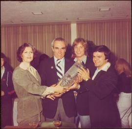 Iona Campagnolo handing celebratory vase to two unidentified men and Marcel Dionne after the Inte...