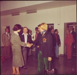 Iona Campagnolo shakes hands with unidentified man while several others look on after the Interna...