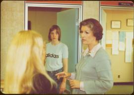 Iona Campagnolo speaking with an unidentified girl in classroom, while another unidentified girl ...
