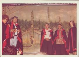 Chief Skidegate Dempsey Collinson, Minister Iona Campagnolo, and three unidentified individuals stand on a stage in button blankets; mural of longhouses and totem poles in background, Haida Gwaii, 1978
