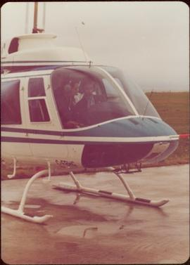 Iona Campagnolo sitting in copilot seat next to unidentified pilot in helicopter on landing strip