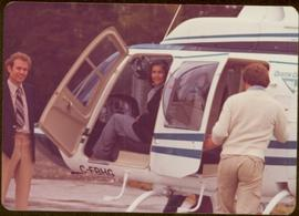 "Iona Campagnolo sitting in copilot seat and two unidentified men standing beside helicopter with a ""Queen Charlotte"" emblem on the side"