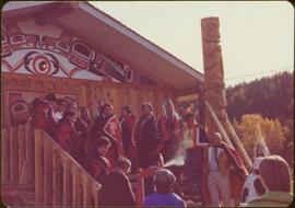 Skeena Riding tour - Group shot of unidentified men and women wearing button blankets in front of longhouse and newly raised totem pole, Kispiox, BC