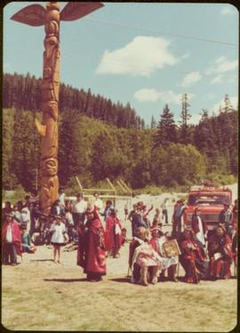 Skeena Riding tour - Distance shot of totem pole flanked by unidentified men, women, and children, some in button blankets