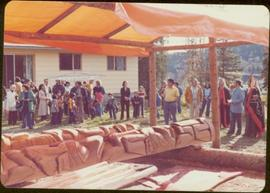 Skeena Riding tour - Iona Campagnolo and unidentified crowd stand around two newly carved totem p...