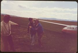 Skeena Riding tour - Iona Campagnolo and two unidentified men pulling a glider through a field with a rope