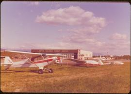 "Skeena Riding tour - Small aircraft and gliders lined up in front of building labeled ""British Co..."