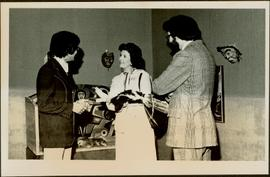 Minister Iona Campagnolo holds a fur craft while speaking with two unidentified men in the Arts and Crafts Division of an unidentified institution