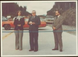 Minister Iona Campagnolo stands next to two unidentified men behind blue ribbon at the opening of Scott Road to Fairview Terminal, Prince Rupert