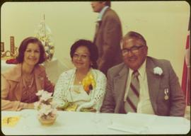 Iona Campagnolo, Mrs. Maitland, and Herbert Maitland seated at table in Kitamaat, BC