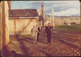 Iona Campagnolo and several unidentified others walk past totem poles and longhouses at 'Ksan, BC