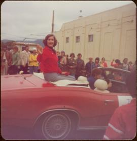 Iona Campagnolo waves from the back of a red convertible as she is driven through parade