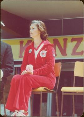 Iona Campagnolo sits on a chair in a jogging suit, holding a rose, Kitimat, BC