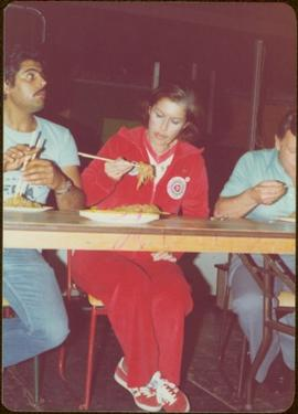 Iona Campagnolo sits on a chair in a jogging suit, eating chow mein with chop sticks at cookoff in Kitimat, BC