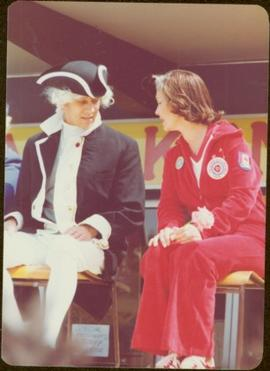 Iona Campagnolo sits on chair in a jogging suit, speaking to a man in George Vancouver costume