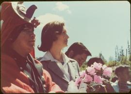 Holding a bouquet of pink silk roses, Iona Campagnolo stands next to an unidentified man in dancing regalia, Kitimat, BC