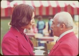 Commonwealth Games, Edmonton 1978 - Iona Campagnolo speaks to an unidentified man, both in red sp...