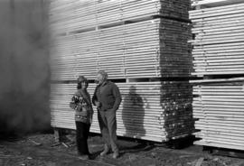 Iona Campagnolo with hard hat speaking with man in front of wood at sawmill owned by Rim Forest P...