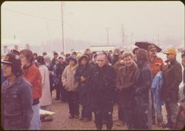 Raising of Eli Gosnell's Pole, New Aiyansh, November 1978 - Iona Campagnolo stands outside in snow with crowd of unidentified people