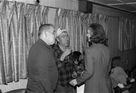 Iona Campagnolo speaking with men, possibly at Kitimat Elks Lodge
