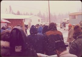 Raising of Eli Gosnell's Pole, New Aiyansh, November 1978 - Unidentified crowd stands outside bet...