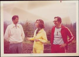 Minister Iona Campagnolo wears a jogging suit while standing outside with two unidentified men, K...