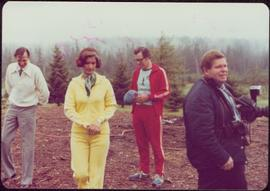 Minister Iona Campagnolo wears a jogging suit while standing outside with two unidentified men and a photographer, Kitimat, BC