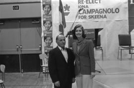 Iona Campagnolo posing with man in front of podium for her Liberal re-election campaign