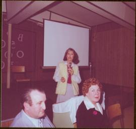 Iona Campagnolo speaking into a microphone behind Bunne Hoffman and unidentified man in Chetwynd, BC