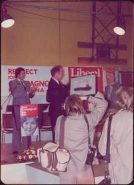 Prime Minister Pierre Trudeau accepts a painting of a fishing boat on stage at Campaign opener in...