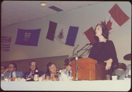 Canada Winter Games, Brandon, MB - Iona Campagnolo speaks at podium set on banquet table, unidentified men and women on left