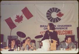 Canada Winter Games, Brandon, MB - Iona Campagnolo speaks at podium set on banquet table, with unidentified woman and men sitting beside her