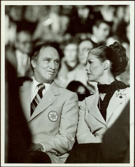 Canada Winter Games, Brandon, MB - Prime Minister Pierre Trudeau and Iona Campagnolo sit in navy and pale blue uniforms in crowded auditorium or arena at the opening of the games