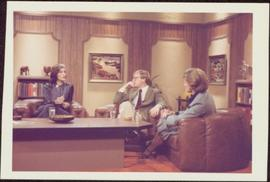 Iona Campagnolo sits with unidentified man and woman around coffee table in CBC television studio