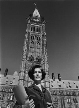 Iona Campagnolo holding folders and standing in front of Peace Tower in Liberal publicity portrait