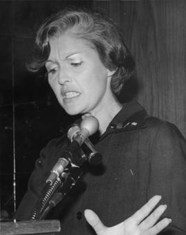 Iona Campagnolo gesturing with hand while speaking at microphone in Liberal publicity image