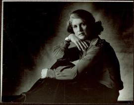 CBC Publicity Photos - Iona Campagnolo facing left, with one hand on her knee and one hand folded beneath her chin