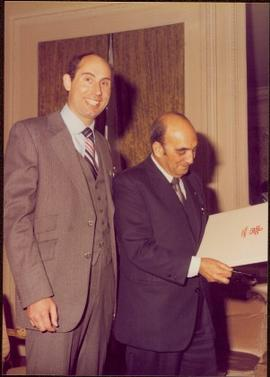 Paris Press Conference - Roger Jackson stands smiling next to an unidentified man holding a Calga...