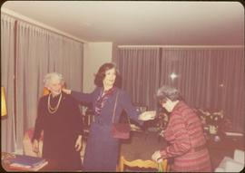 Iona Campagnolo standing in living room with unidentified woman and Thérèse Casgrain, Quebecois feminist and former senator