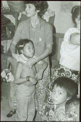 CUSO Mission, North-eastern Thailand - Unidentified woman putting a shirt on a young girl in fron...