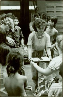CUSO Mission, North-eastern Thailand - Unidentified woman offers a tray to another woman in group