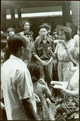 CUSO Mission, North-eastern Thailand - Unidentified woman in group lifts a cup in a demonstration